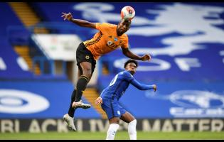 Chelsea's Willian (right) watches Wolverhampton Wanderers' Willy Boly leaping for a header during the English Premier League match between Chelsea and Wolverhampton Wanderers at Stamford Bridge in London, July 26, 2020.