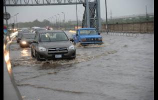 Vehicles traversing Marcus Garvey Drive, in the vicinity of Tinson Pen, following torrential rain .