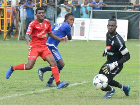 File Amal Knight (right), goalkeeper from UWI FC, looks on as the ball rolls past the goalpost from a shot by Kemar Beckford (centre) from Mount Pleasant, during the second-leg semi-finals of the Red Stripe Premier League football.